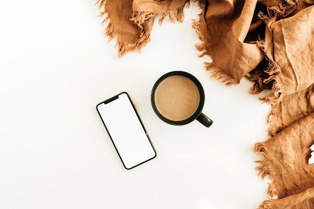 一杯のコーヒー、オレンジ色の毛布、白い表面に空白の画面が表示されたスマートフォン。フラットレイ、上面図