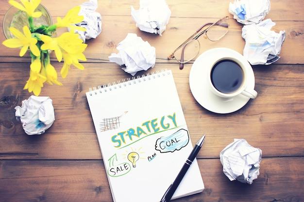 나무 테이블에 커피, 펜, 메모장, 종이, 안경, 꽃 한 잔
