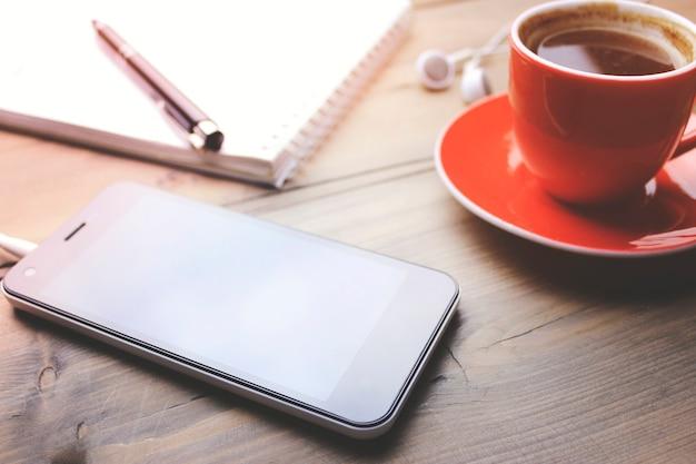 一杯のコーヒー、電話、イヤホン、ノートブック、木製のテーブルの上のペン