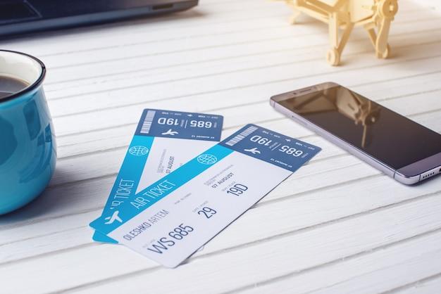Чашка кофе билеты на самолет, телефон и ноутбук на белом деревянном фоне