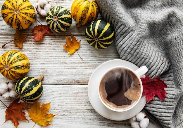 Чашка кофейных тыкв и сухих листьев
