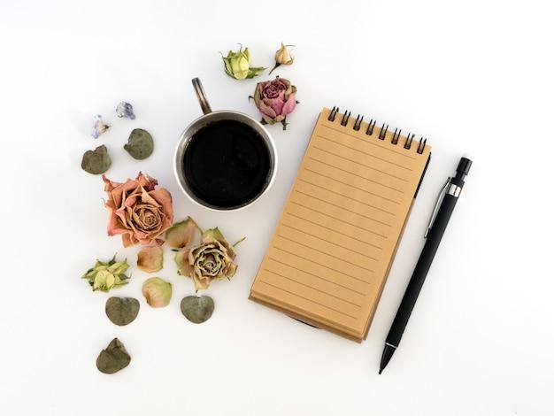 一杯のコーヒー、スケッチブック、鉛筆、ドライフラワー。