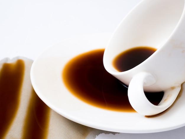 Чашка кофе разлила на белой предпосылке, взгляд сверху. для гранж рекламы, скопируйте пространство