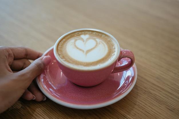 Чашка кофе стоя на деревянном столе. крупным планом рука держит чашку ароматного капучино в кафе