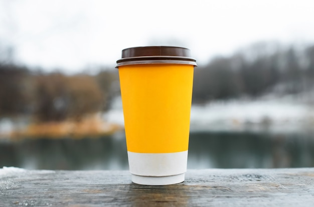 屋外の木製テーブルの上に立っているコーヒーのカップ、クローズアップ。冬の背景に黄色の紙ガラス。