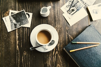 Cup of coffee stands on wooden table among all photos