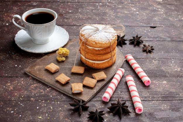 木製のフルーツベイクケーキビスケットスウィートにクッキーとサンドイッチクッキーと一緒に強くて熱いコーヒーのカップ