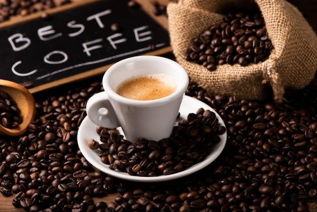 コーヒー豆に囲まれた一杯のコーヒーがクローズアップ