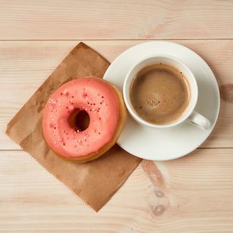 Чашка кофе, сладкий пончик с розовой глазурью вид сверху деревянный фон