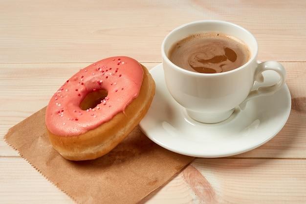 Чашка кофе, сладкий пончик с розовой глазурью на деревянном фоне