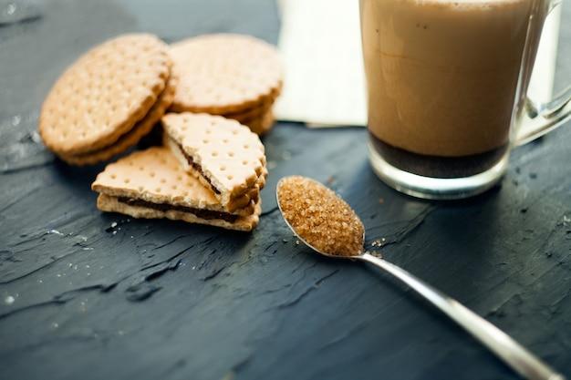 초콜릿 달콤한 디저트와 함께 제공되는 쿠키와 갈색 슈가를 곁들인 커피 한 잔
