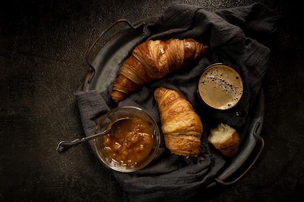 어두운 나무 쟁반에 크루아상을 넣은 커피 한 잔.