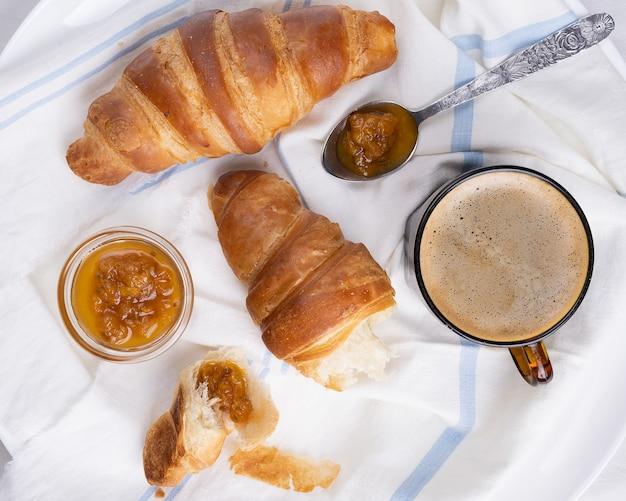 Чашка кофе с круассаном на белом деревянном подносе.