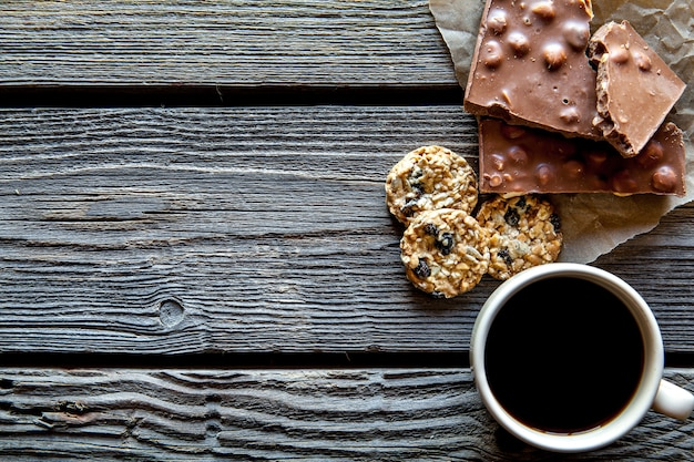 Чашка кофе с вкусным шоколадом и печеньем на деревянном фоне