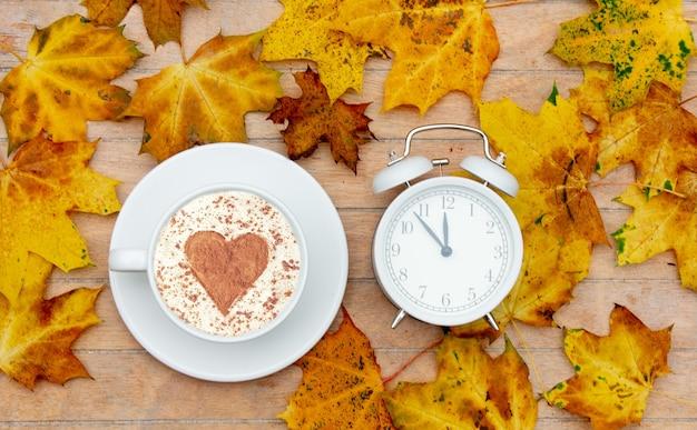 テーブルの上にシナモンと目覚まし時計のハートが付いた一杯のコーヒー、カエデの葉が周りに