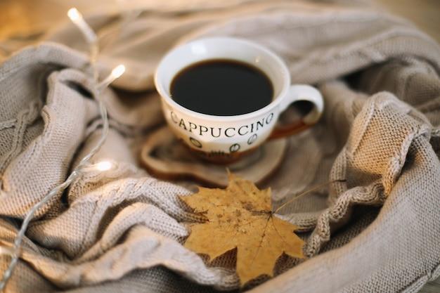 Чашка кофе с вязаным бежевым пледом на фоне концепция осенне-зимнего досуга