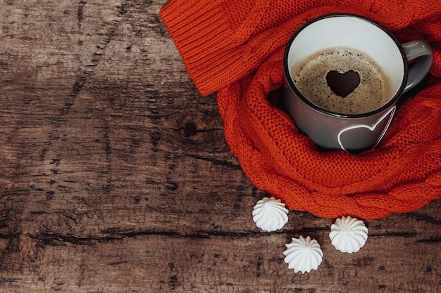 木製のテーブルに塗られた心とコーヒーのカップ