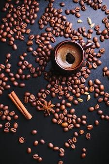 Чашка кофе с россыпью кофейных зерен на темноте