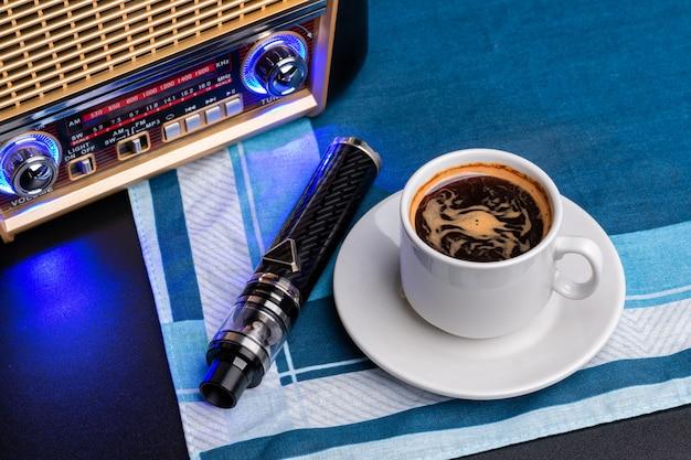 Чашка кофе с vaping устройством на черном фоне