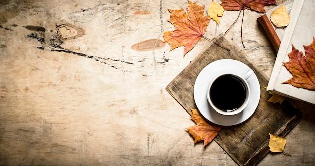 古い本とカエデの葉とコーヒーのカップ。木製の背景に。