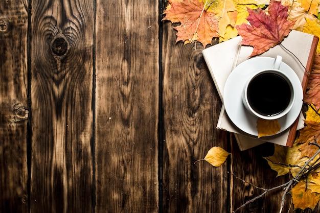 古い本と木製の背景にカエデの葉とコーヒーのカップ