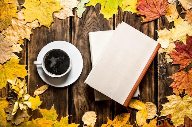 古い本とカエデの葉とコーヒーのカップ