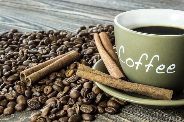 木製のテーブルに豆とシナモンスティックとコーヒーのカップ