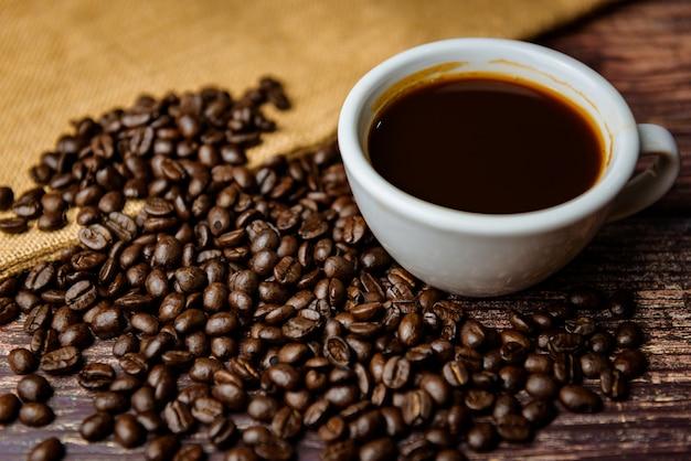 Чашка кофе с фасолью на деревянном фоне