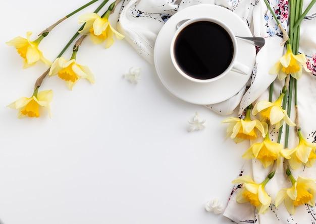 흰색 테이블에 아름다운 수선화 꽃과 커피 한잔