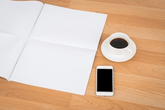 Cup of coffee with blank papers and smartphone