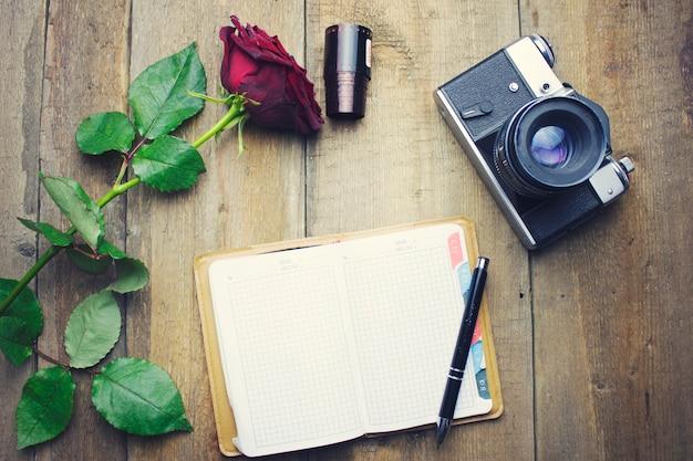 木製のテーブルにカメラとノートブックとコーヒーのカップ