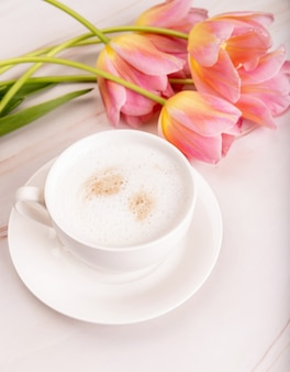 大理石の背景にチョコレートとピンクのチューリップとコーヒーのカップ