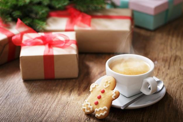 Чашка кофе с рождественским печеньем на деревянном столе