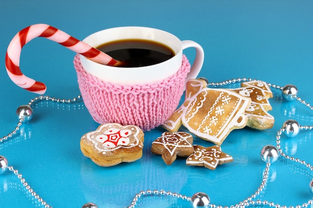 Чашка кофе с рождественской сладостью на синей стене