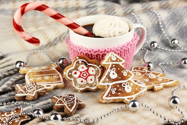 格子縞のクローズアップにクリスマスの甘さのコーヒーのカップ