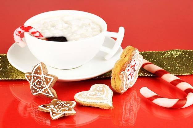Чашка кофе с рождественской сладостью на красном фоне