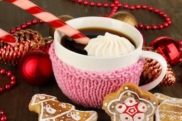 Чашка кофе с рождественской сладостью на деревянном столе крупным планом