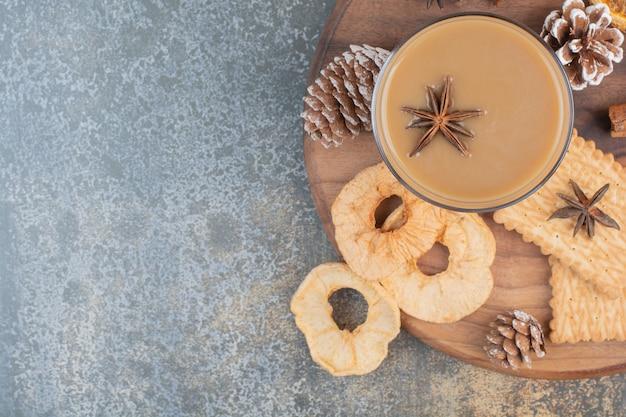 Чашка кофе с палочками корицы и шишками на деревянной тарелке. фото высокого качества