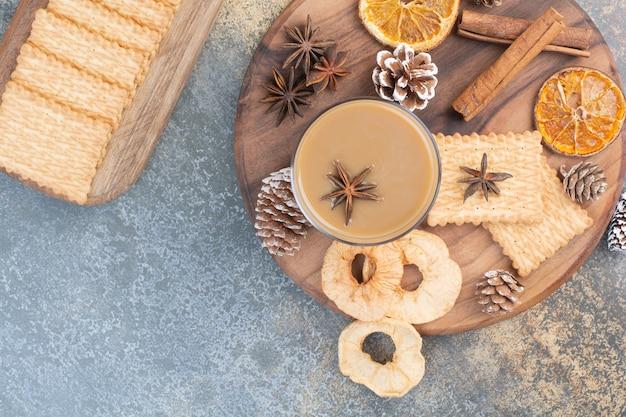 木の板にシナモンスティックと松ぼっくりとコーヒーのカップ。高品質の写真