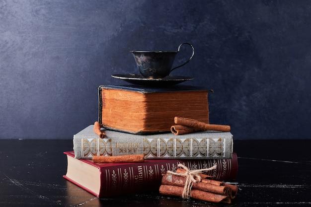 Чашка кофе с палочками корицы.