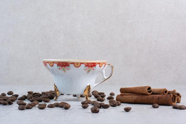 Чашка кофе с кофейными зернами и палочками корицы. фото высокого качества