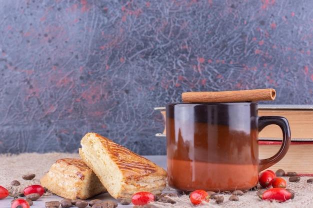 Чашка кофе с кофейными зернами и выпечкой на мешковине. фото высокого качества