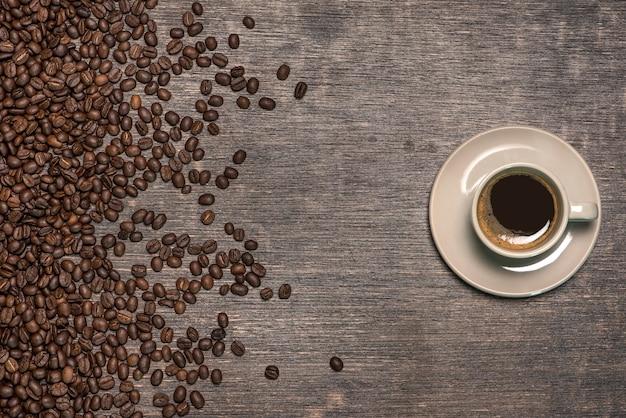 古いテーブルの上のコーヒー豆とコーヒーのカップ
