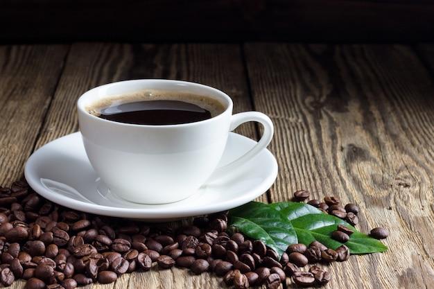 나무 배경에 원두 커피와 커피 한잔