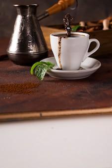石の背景にコーヒーとスパイスの穀物とココア豆とコーヒーのカップ