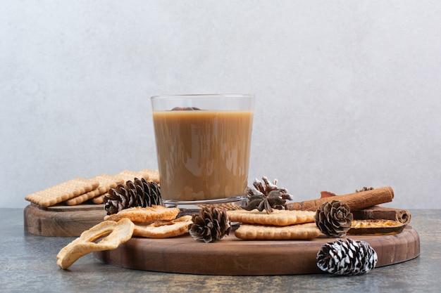 Чашка кофе с печеньем и шишками на деревянной тарелке. фото высокого качества
