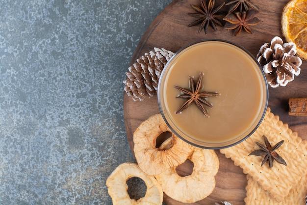木製のプレートにクッキーと松ぼっくりとコーヒーのカップ。高品質の写真
