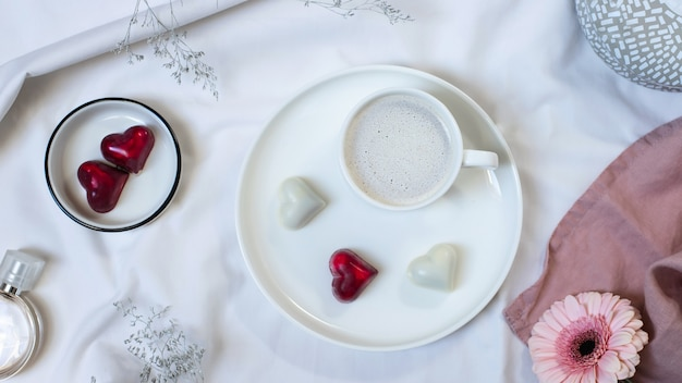 Чашка кофе с кремом, конфеты и цветы на белой кровати. завтрак в постель для любимой жены плоская планировка, вид сверху, концепция дня святого валентина