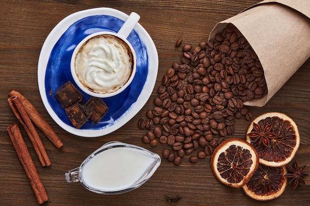 어두운 나무 테이블에 크림 커피 콩 초콜릿과 향신료를 넣은 커피 한 잔. 세계 커피의 날