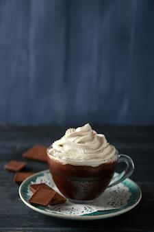 色の木製の背景にクリームとコーヒーのカップ